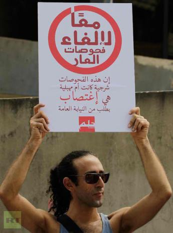 "Lebanese demonstrator holds a sign reading ""Together for the elimination of tests of shame, these tests are rape"" during a protest against anal ""tests"" on men suspected of homosexuality and so-called ""virginity tests"" for women in Beirut on August 11, 2012. (AFP Photo / Anwar Amro)"