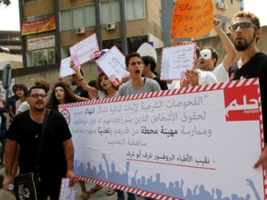 "Lebanese demonstrators hold signs against anal ""tests"" on men suspected of homosexuality and so-called ""virginity tests"" for women during a protest in Beirut on August 11, 2012 (AFP Photo / Anwar Amro)"